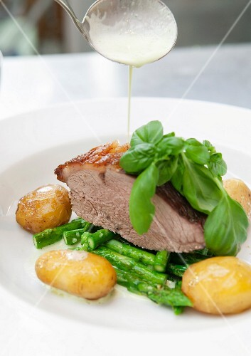 Roast pork with green asparagus, potatoes and basil