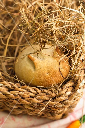 A rabbit-shaped bread roll with a carrot in an Easter basket