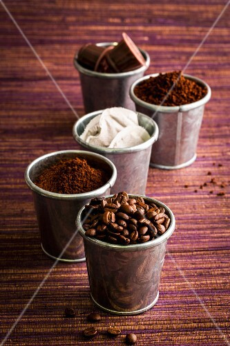 Various types of coffee: coffee beans, powder, capsules and sachets in metal cups