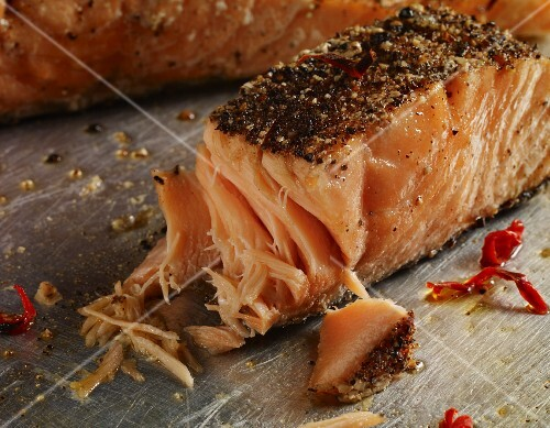 Grilled salmon fillet with a black pepper coating and chillis (close-up)