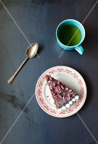 A slice of chocolate cake with pomegranate seeds and marshmallows