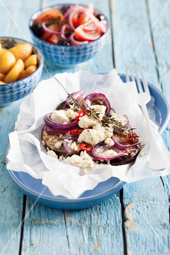 Greek aubergines with red onions and feta cheese in parchment paper