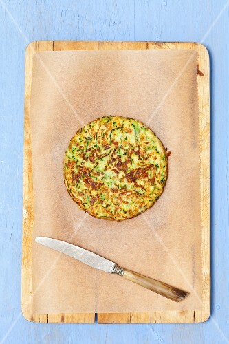A courgette cake on baking paper with a knife