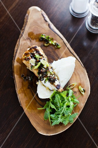 Fish with mashed potatoes and rocket on a wooden board
