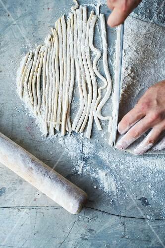 Homemade tagliatelle being cut