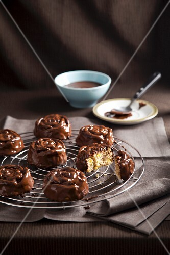 Mini babas with bananas, rum and chocolate glaze on a wire rack