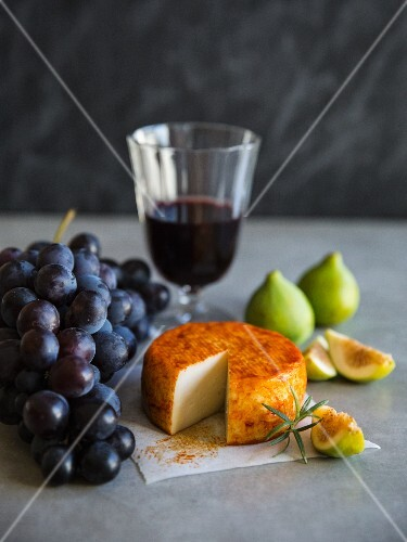 An arrangement of grapes, wine, cheese and figs