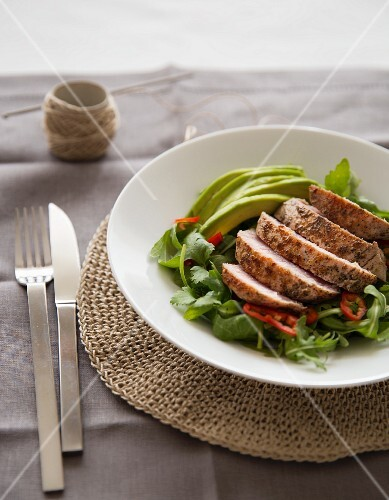 Grilled tuna on a bed of lettuce with avocado and peppers