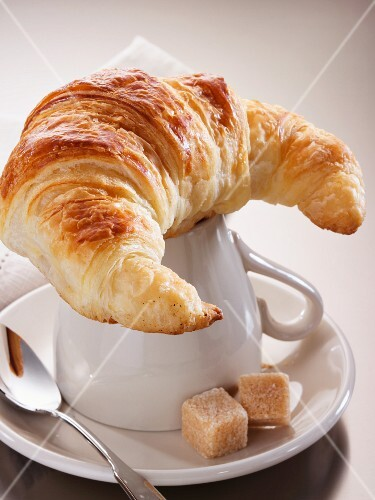 A croissant on top of a coffee cup