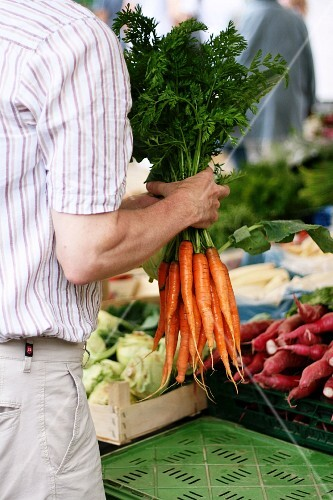 A man with a bunch of fresh carrots at a market
