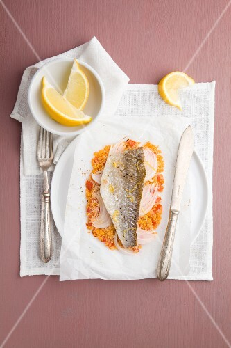 Sea bass on a bed of couscous and onions in parchment paper