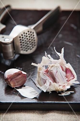 An arrangement featuring garlic and a garlic press