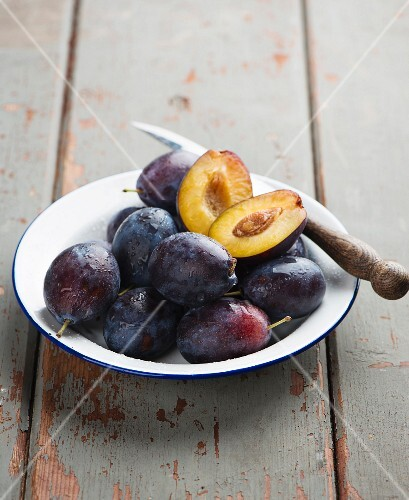 A plate of fresh damsons with a knife