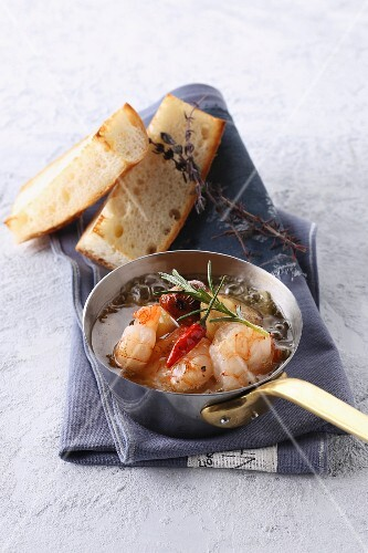 Prawns with chilli peppers in a pan served with white bread