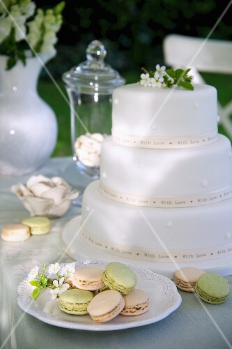 White, multi-tiered wedding cake and macaroons