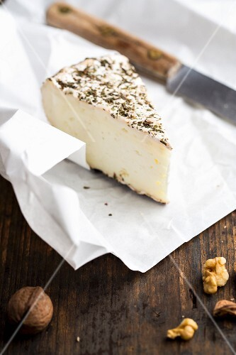 Goat's cheese with herbs on a piece of paper with a knife and walnuts