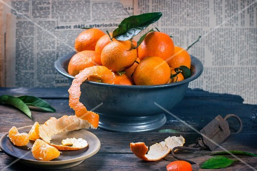 An arrangement of clementines in a metal bowl on a rustic wooden table
