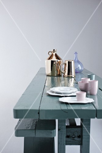 China, glass and shiny chrome tableware on rustic wooden table painted grey