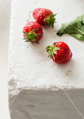 Three strawberries on a white surface