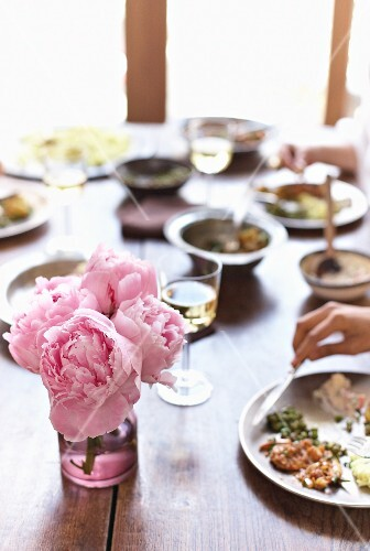 Table set with Indian food and peonies