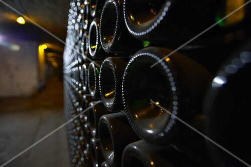 A close-up of bottle bottoms in an aisle of a wine cellar