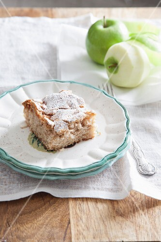 A slice of apple crumble cake with icing sugar