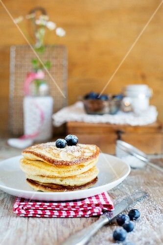 A stack of pancakes with sugar and blueberries