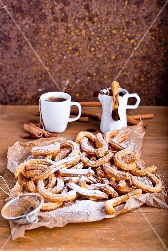 Churros with icing sugar and a chocolate dip