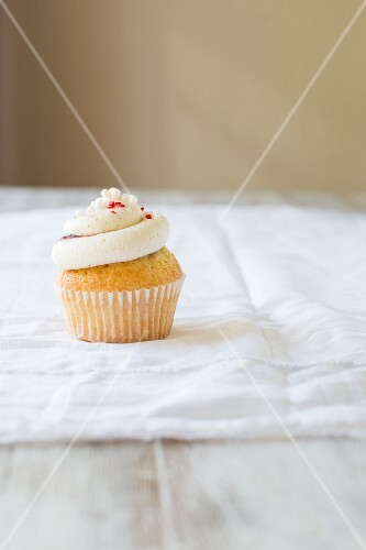 A vanilla cupcake topped with a vanilla cream, berries and sprinkles