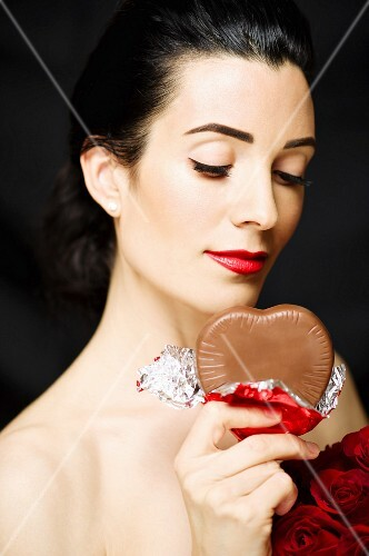 A dark haired woman holding a chocolate heart
