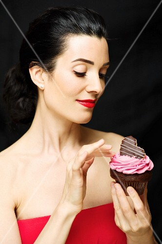 A dark haired woman wearing a red cocktail dress holding a cupcake