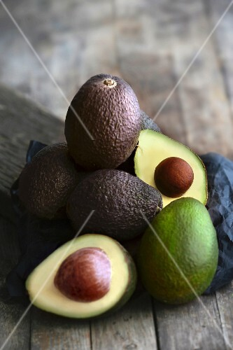 A stack of avocados on a dark wooden surface