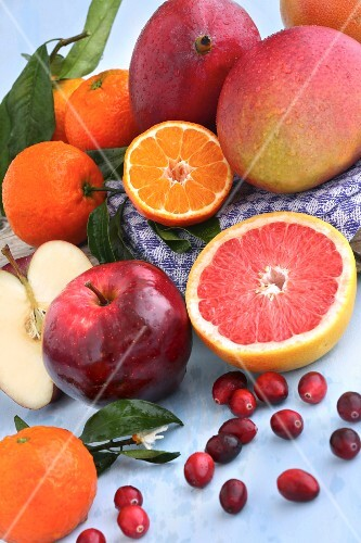 Apples, grapefruits, mangos, cranberries and clementines on a light blue surface with a tea towel