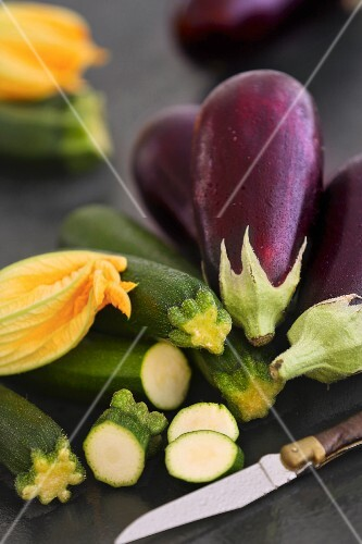 Aubergines and courgettes with flowers on a dark surface