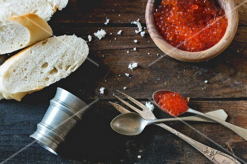 Red caviar in a wooden bowl with bread and old cutlery