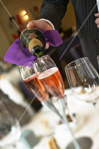 A waiter pouring rosé sparkling wine in a restaurant