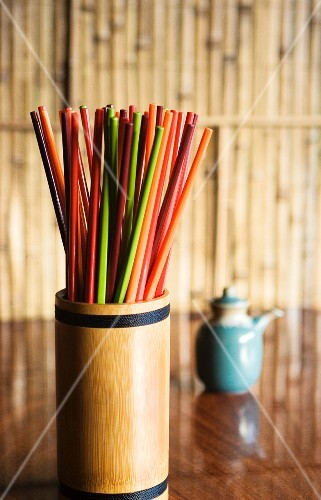 Colourful chopsticks in a bamboo container on a table in a restaurant