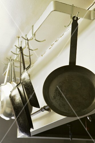 Metal pans hanging on hooks in a restaurant kitchen