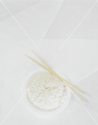 Steamed rice in a white bowl on a white surface