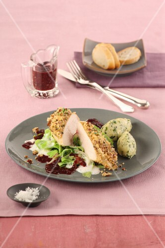 Roasted corn poularde breast with a pecan nut crust on cherry sauce with creamy cabbage and herb semolina dumplings