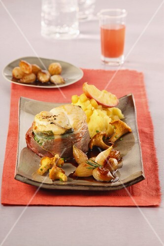 Fried monkfish medallions wrapped in bacon served with pearl onions on a bed of mashed apples and potatoes