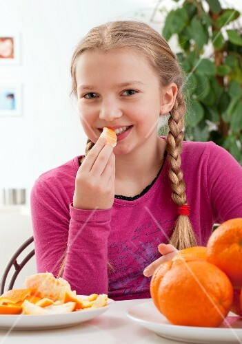 A girl eating an orange