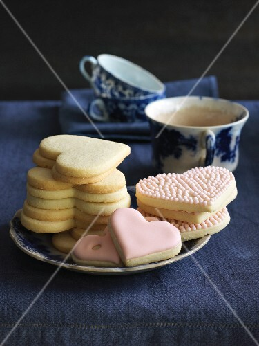 Heart-shaped cookies with pink icing served with tea