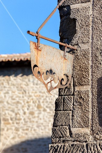 Metal sign hanging on a building in the Citadel of Carcassonne (France)