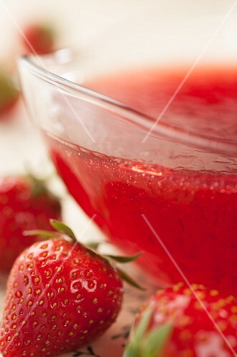 Strawberry jam in a glass bowl with fresh strawberries