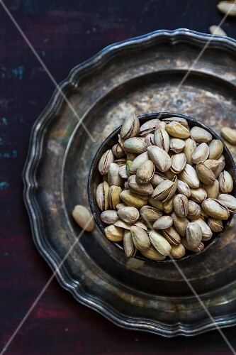 A bowl of pistachios on a pewter plate