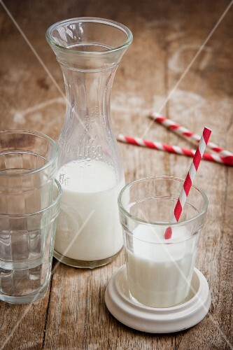 Milk in carafe and a glass with striped straws