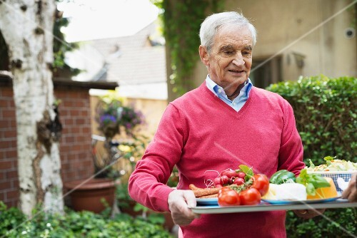An old man carrying a tray of food into a garden