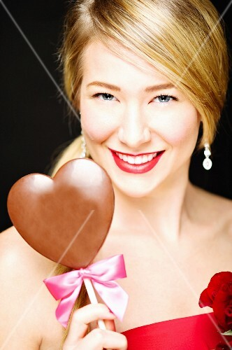 A young blonde woman holding a heart-shaped lolly