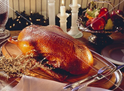 Goose with dumpling stuffing on a wooden board with a carving set